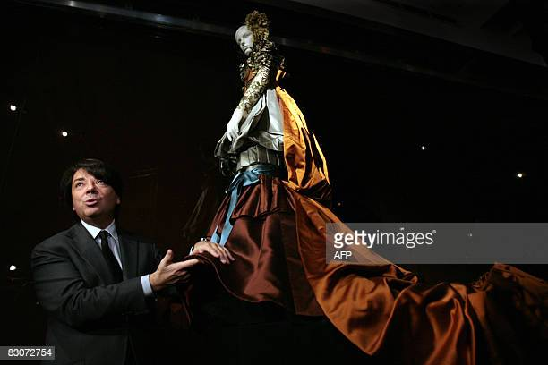 Russian fashion designer Valentin Yudashkin touches a dress of his model during an exhibition in the State historical museum at Red Square in Moscow...