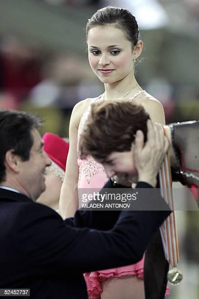 US Sasha Cohen looks at Russia's Irina Slutskaya receiving her gold medal from IOC member and President of the International Figure Skating...