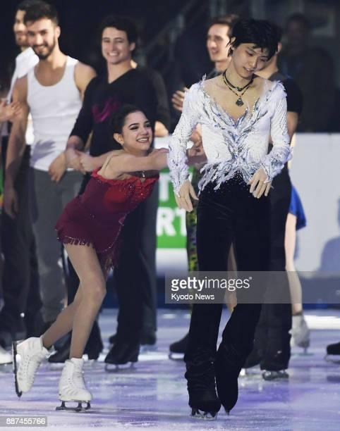Russian figure skater Evgenia Medvedeva nudges Yuzuru Hanyu of Japan to perform an encore during the Grand Prix Final gala exhibition in Marseille...