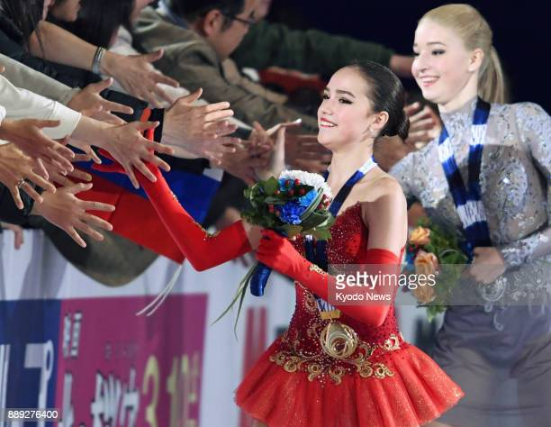 Russian figure skaters Alina Zagitova and Maria Sotskova exchange high fives with spectators after winning the gold and the silver respectively at...