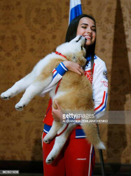 Russian figure skating gold medallist Alina Zagitova holds an Akita Inu puppy named Masaru in her arms presented by Japanese Prime Minister in Moscow...