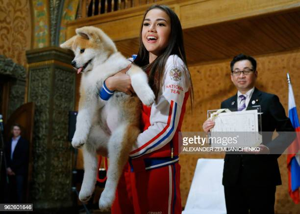 Russian figure skating gold medallist Alina Zagitova holds an Akita Inu puppy named Masaru presented by Japanese Prime Minister in Moscow on May 26...
