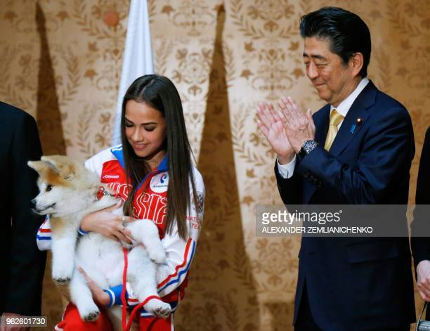 Russian figure skating gold medallist Alina Zagitova holds an Akita Inu puppy named Masaru presented by Japanese Prime Minister Shinzo Abe in Moscow...