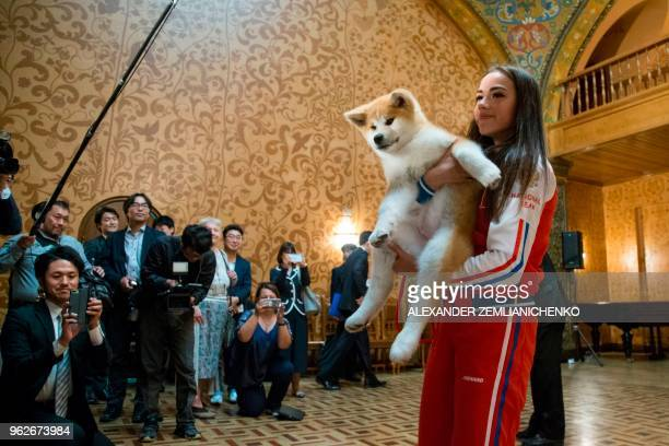 Russian figure skating gold medallist Alina Zagitova holds an Akita Inu puppy named Masaru in her arms after it was presented by Japanese Prime...