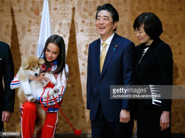 TOPSHOT Russian figure skating gold medallist Alina Zagitova Japanese Prime Minister Shinzo Abe and his wife Akie Abe poses with an Akita Inu puppy...