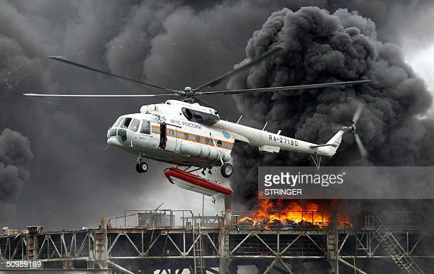 Russian fire helicopter flies over the burning oil rig during the Russia and NATO joint military exercises near Kaliningrad 23 June 2004 Military...
