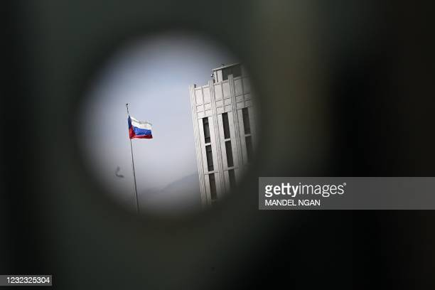 Russian flag at the Embassy of Russia is seen through a bus stop post in Washington, DC on April 15, 2021. - The US announced sanctions against...