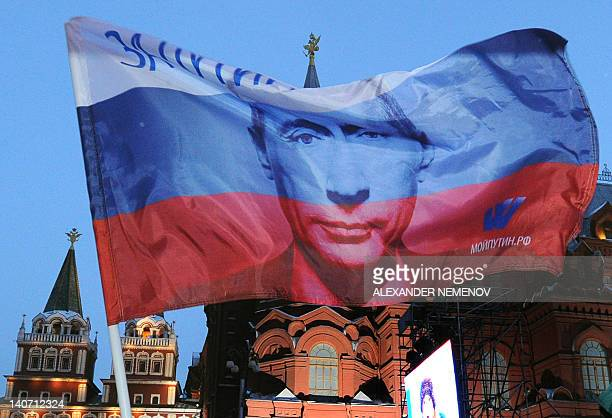A Russian flag featuring Prime Minister Vladimir Putin flies above his supporters as they celebrate Putin's victory as they rally at the central...