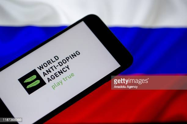 Russian flag is seen behind as World Anti-Doping Agency logo is displayed on a smart phone screenin this illustration photo in Ankara, Turkey on...