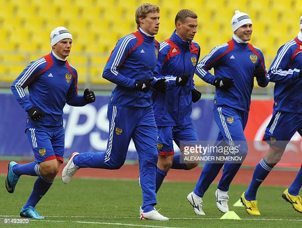 Russian footballers Andrei Arshavin Pavel Pogrebnyak Aleksei Berezutsky and goalkeeper Igor Akinfeev warm up during a training session in Moscow on...