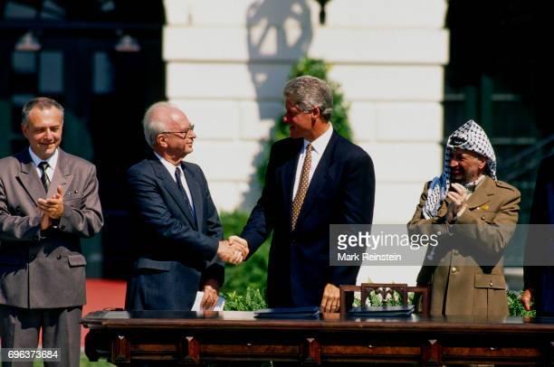 Russian Foreign Minister AndreI Kozyrev and Palestine Liberation Organization Chairman Yasser Arafat applaud, Israeli Prime Minister Yitzhak Rabin...