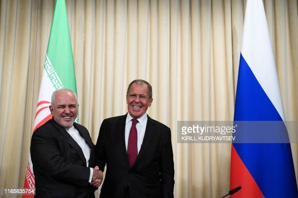 Russian Foreign Minister Sergei Lavrov and his Iranian counterpart Mohammad Javad Zarif shake hands following a meeting in Moscow on September 2,...