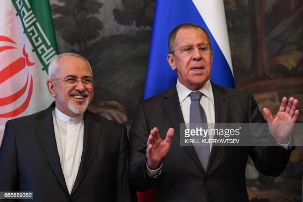 Russian Foreign Minister Sergei Lavrov gestures next to his Iranian counterpart Mohammad Javad Zarif during a family photo ahead of a meeting of...