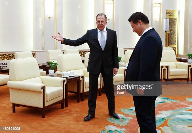 Russian Foreign Minister Sergei Lavrov gestures to Chinese President Xi Jinping for the arrival of Russian delegates during a meeting at the Great...