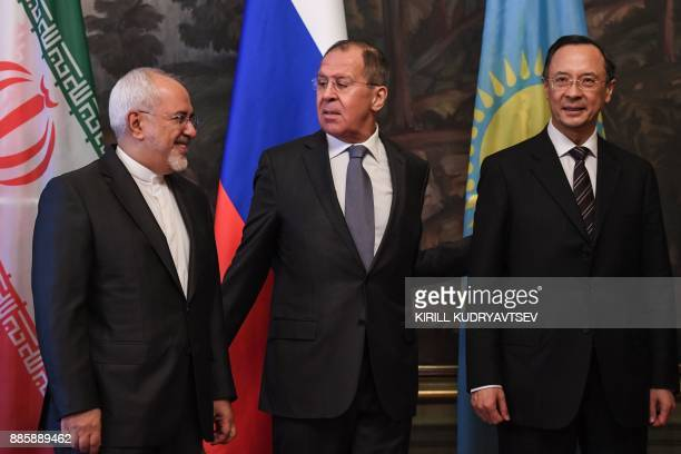 Russian Foreign Minister Sergei Lavrov looks at his Iranian counterpart Mohammad Javad Zarif as they stand next to Kairat Abdrakhmanov of Kazakhstan...