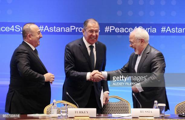 Russian Foreign Minister Sergei Lavrov shakes hands with Iranian Foreign Minister Mohammad Javad Zarif and Turkish Foreign Minister Mevlut Cavusoglu...