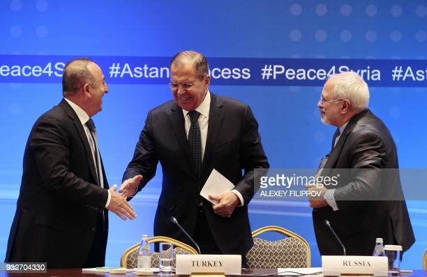 Russian Foreign Minister Sergei Lavrov shakes hands with Turkish Foreign Minister Mevlut Cavusoglu and Iranian Foreign Minister Mohammad Javad Zarif...