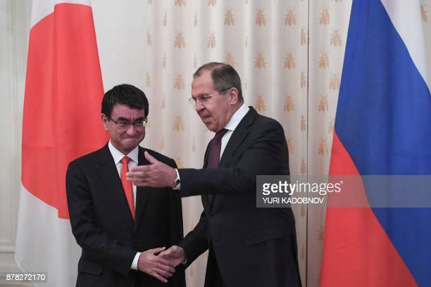 Russian Foreign Minister Sergei Lavrov shows the way his Japan's counterpart Taro Kono during a meeting in Moscow on November 24, 2017. / AFP PHOTO /...