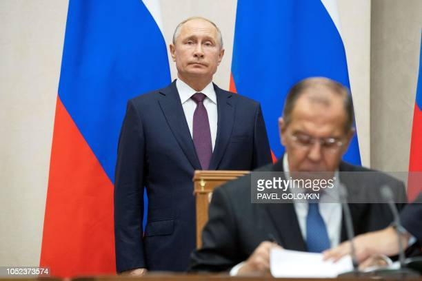 TOPSHOT Russian Foreign Minister Sergei Lavrov signs documents as Russian President Vladimir Putin attends a signing ceremony following his talks...