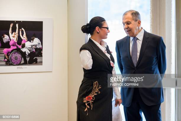 Russian Foreign Minister Sergei Lavrov speaks with Russian amputee athlete Elena Volokhova during the opening of a photo exhibition on disabled...