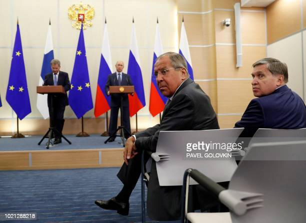 Russian Foreign Minister Sergey Lavrov and Kremlin foreign affairs adviser Yuri Ushakov look at the media as Russian President Vladimir Putin and...