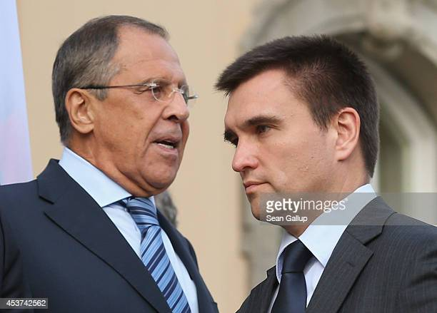 Russian Foreign Minister Sergey Lavrov and Ukrainian Foreign Minister Pavlo Klimkin pass by one another while arriving for a group photo with French...