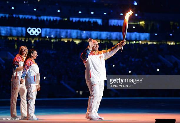 Russian former wrestler Alexander Karelin holds up the Olympic torch during the Opening Ceremony of the Sochi Winter Olympics at the Fisht Olympic...