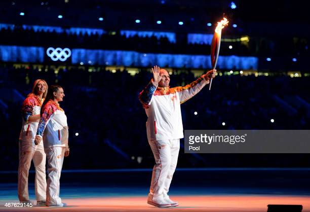 Russian former wrestler Alexander Karelin holds up the Olympic torch next to Russian pole vaulter Yelena Isinbayeva and Russian tennis player Maria...