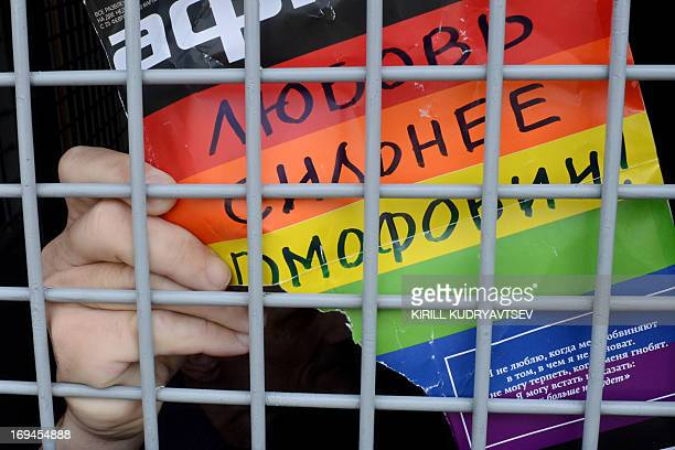 A Russian gay and LGBT rights activist shows sign reading 'Love is stronger than homophobia' from inside of a Russian riot police van during...