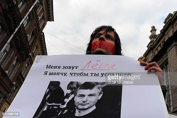 A Russian gay rights activist wearing tape over his mouth holds a placard with a photo of journalist and theatre critic Dmitry Tsilikin during a...