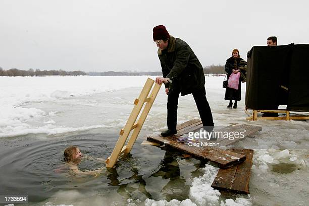 Russian girl submerges himself in the cold water during a ceremony for the Orthodox Epiphany on the banks of the Moscow River January 19 2003 in...