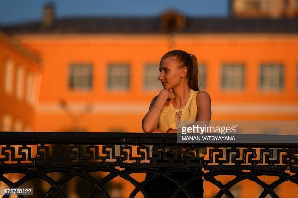 A Russian girl watches the sunset on the banks of the Volga river in Samara on June 19 2018 during the Russia 2018 World Cup football tournament