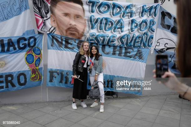 Russian girls have their picture taken in front of flags put up by fans of Argentina in Moscow on June 13 2018 in Moscow Russia