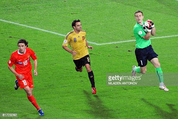 Russian goalkeeper Igor Akinfeev catches the ball in front of Russian midfielder Yuri Zhirkov and Spanish midfielder Xavi Hernandez during the Euro...