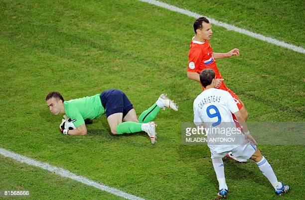 Russian goalkeeper Igor Akinfeev catches the ball next to Russian defender Sergei and Greek forward Angelos Charisteas during the Euro 2008...