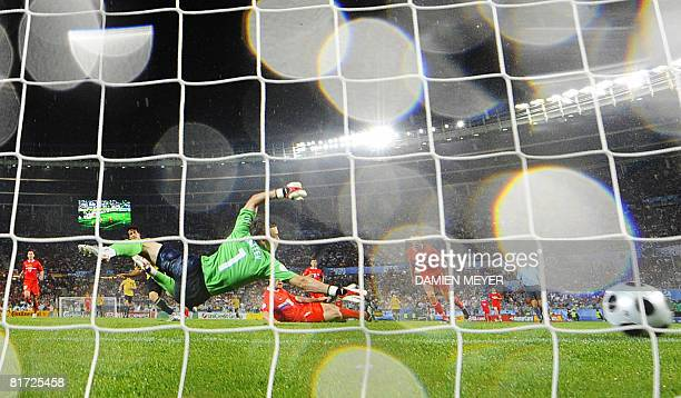 Russian goalkeeper Igor Akinfeev dives but misses the shot of Spanish midfielder David Silva during the Euro 2008 championships semifinal football...