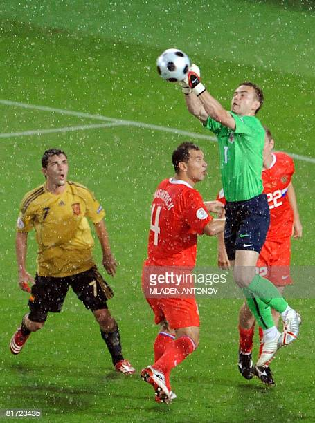 Russian goalkeeper Igor Akinfeev jumps for the ball in front of Russian defender Sergei Ignashevich Russian defender Alexander Anyukov and Spanish...