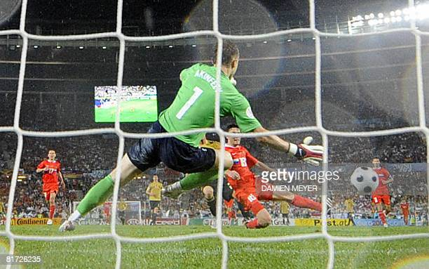 Russian goalkeeper Igor Akinfeev leaps for the ball but misses as Spanish midfielder David Silva scores during the Euro 2008 championships semifinal...