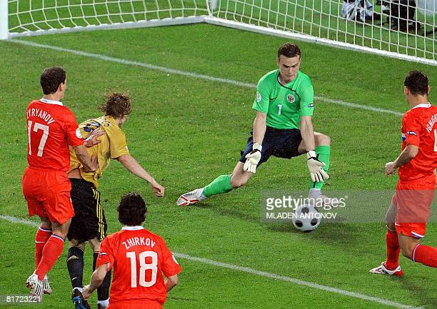 Russian goalkeeper Igor Akinfeev stops a ball kicked by Spanish forward Fernando Torres during the Euro 2008 championships semifinal football match...
