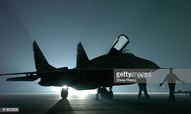 Russian ground crew members stand next to a Mig-29 fighter jet upon its arrival at the Airshow China 2004 on November 1, 2004 in Zhuhai, Guangdong...