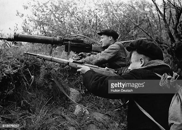 A Russian guerilla fires a confiscated Nazi machine gun while his comrade fires a standard issue rifle
