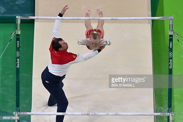 Russian gymnast is helped by a coach after falling from the uneven bars during a practice session of the women's Artistic gymnastics at the Olympic...