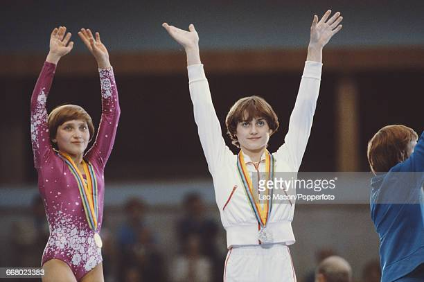 Russian gymnast Yelena Davydova competing for the Soviet Union raises her arms in the air on the podium after finishing in first place to win the...