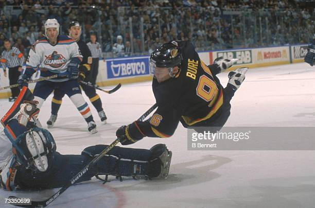 Russian hockey player Pavel Bure of the Vancouver Canucks sails through the air as he tries to score on the New York Islanders goalie, Uniondale, New...