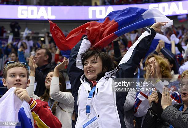 A Russian Ice Hockey supporter reacts after her team scored during the Men's Ice Hockey Group A match USA vs Russia at the Bolshoy Ice Dome during...