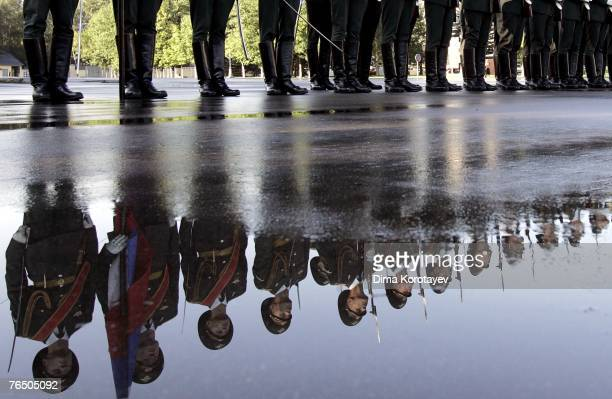Russian Interior Ministry honour guards are reflected in a puddle as they stand during an opening ceremony of the Russian Chinese joint counter...