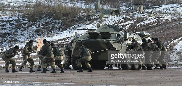 Russian Interior Ministry special team gurads push an APC during military exercises during the Interpolitex exhibition at the polygon of...