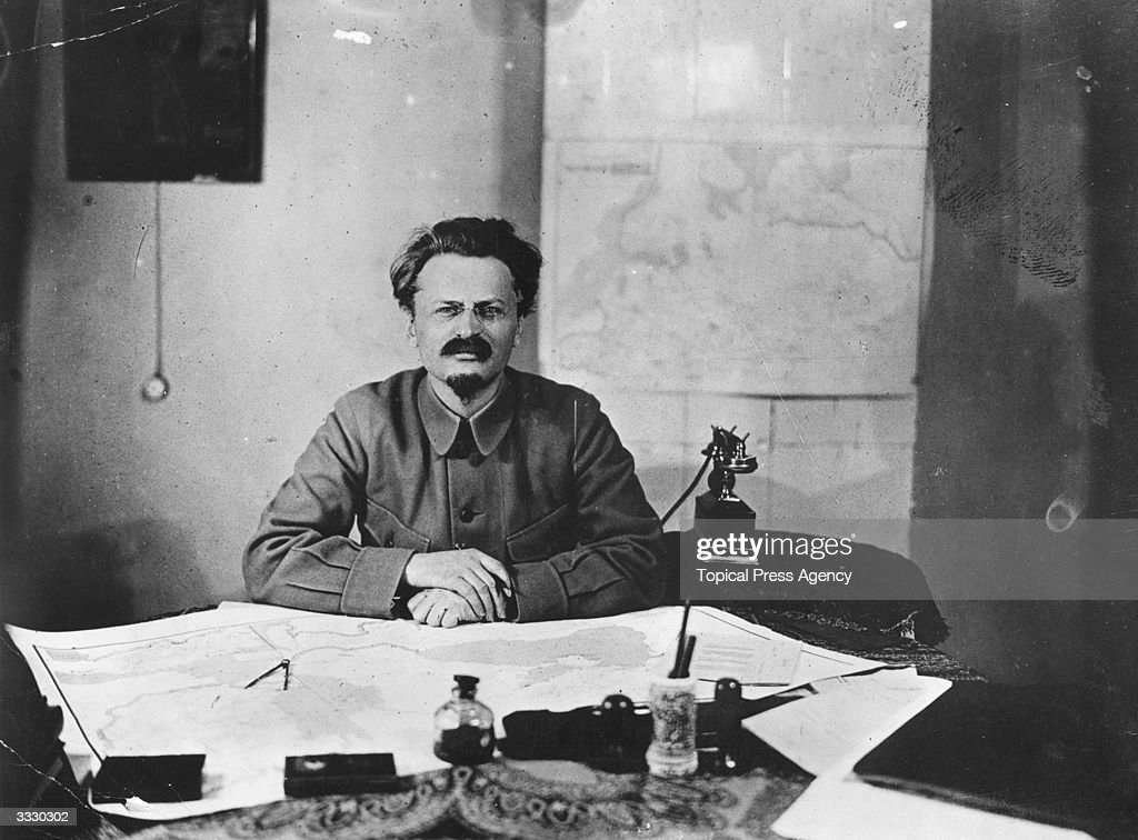 Russian Jewish revolutionary Leon Trotsky (1879 - 1940), real name Lev Davidovich Bronstein, sitting at a desk, where he has been studying a map.