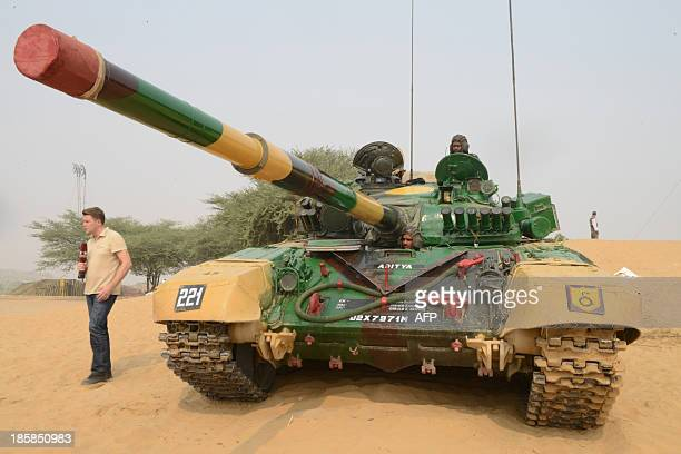 A Russian journalist stands beside an Indian tank supplied by Russia before the INDRA 2013 IndoRussia joint military drill at the Mahajan Field...