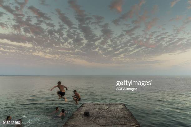 Russian kids jumping into the Black Sea after sunset in Sukhumi Abkhazia is a partially recognized state located in north western Georgia Back in the...